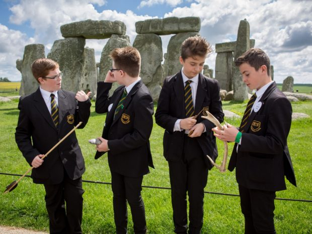 Four school boys standing in front of Stonehenge holding museum objects during their Takeover Day.