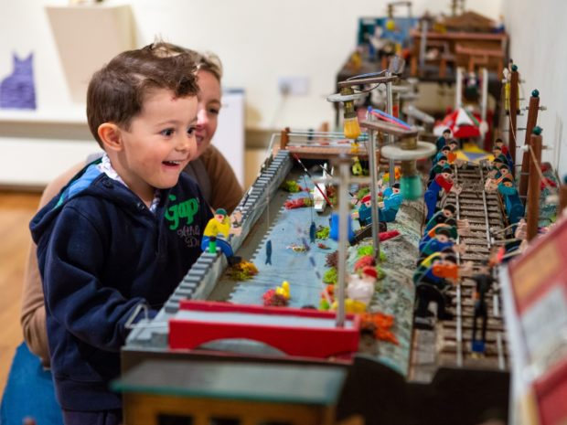 A young boy and his mother playing with a toy model of fishermen and railway workers at Falmouth Art Gallery.