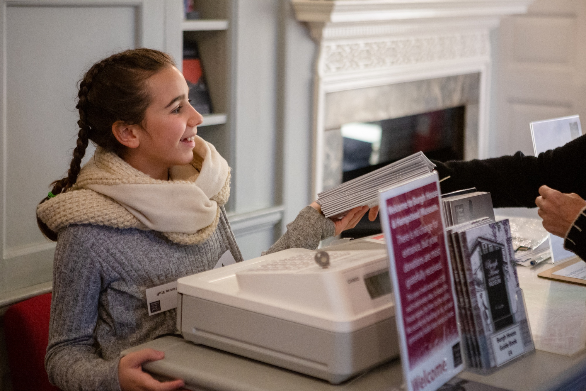 A girl serving a visitor behind the till at Burgh House and Hampstead Museum on Takeover Day.