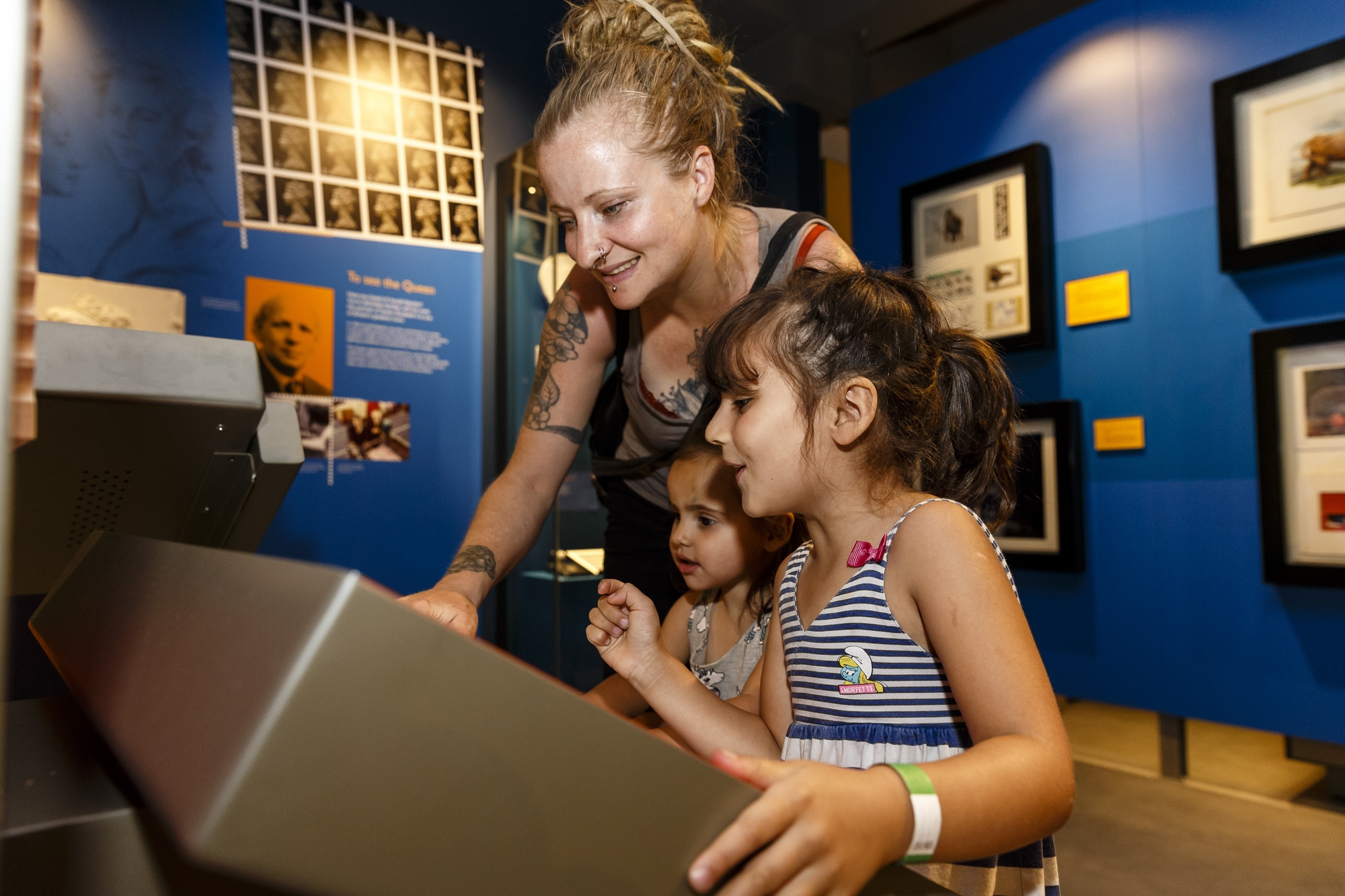A family uses a touchscreen interactive at the Postal Museum.