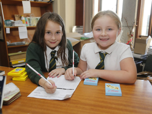 Two schoolgirls smiling as they fill in paperwork in a store room at the National Library of Wales during Takeover Day.