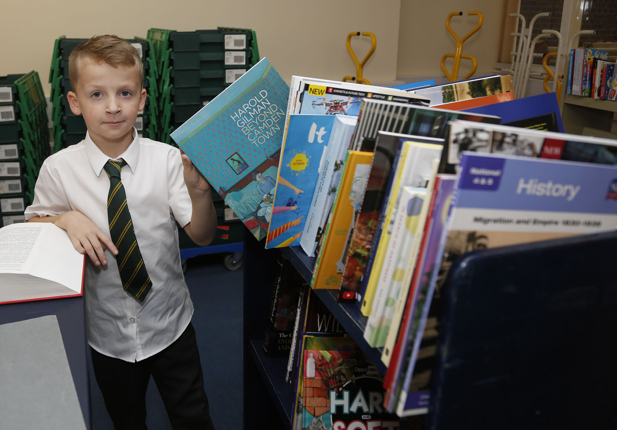 A school boy sorting a bookshelf as librarian at the National Library of Wales Takeover Day.