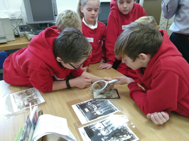 A group of primary school children look at old photographs using a magnifying glass at the Gwynedd Archives Takeover Day.
