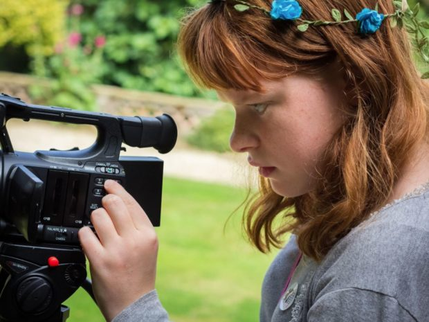 A still from the How I See It film showing a young girl filming with a video camera in a garden.