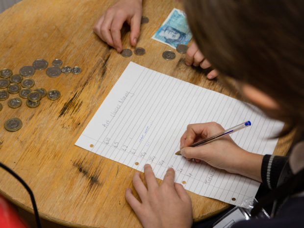 A school child leans on a desk covered with coins and writes on a piece of paper with the heading 'Art Class money' during the Lauderdale House Takeover Day.