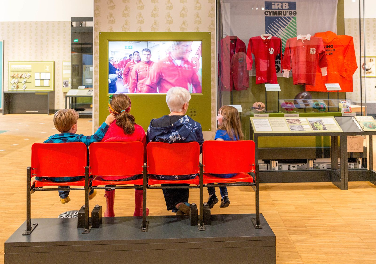 A family sits in front of a video screen at St Fagans National Museum of History.
