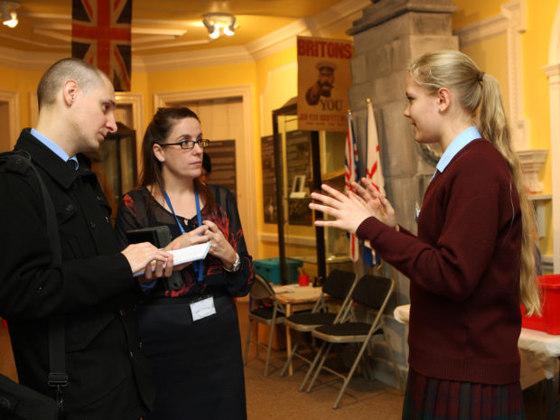 A young woman talking to adult visitors at Lowewood Museum on Takeover Day.