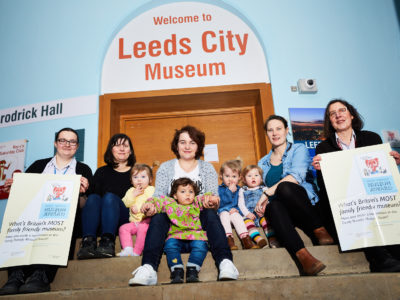Museum staff, toddlers and parents pose in front of the Leeds City Museum reception holding Family Friendly Museum Award posters.