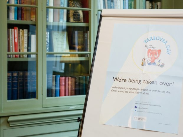 A Kids in Museums Takeover Day poster displayed on an easel next to a bookcase at Burgh House and Hampstead Museum.