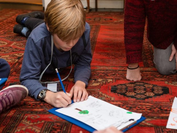 A young boy draws a poster lying on the floor at Burgh House and Hampstead Museum during Takeover Day.
