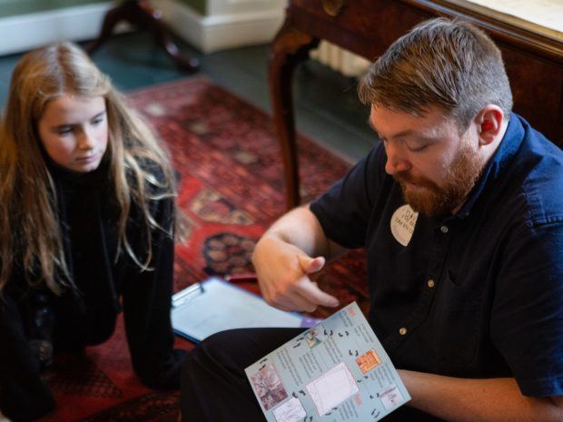 A member of museum staff shows schoolchildren a museum trail at the Burgh House and Hampstead Museum Takeover Day.