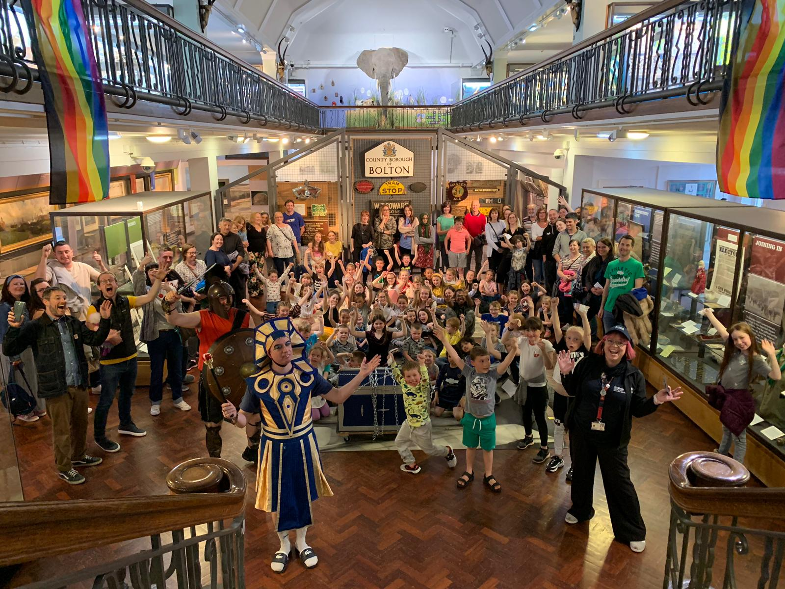 Members of staff and families at Bolton Museum and Art Gallery cheering and waving their arms in celebration.