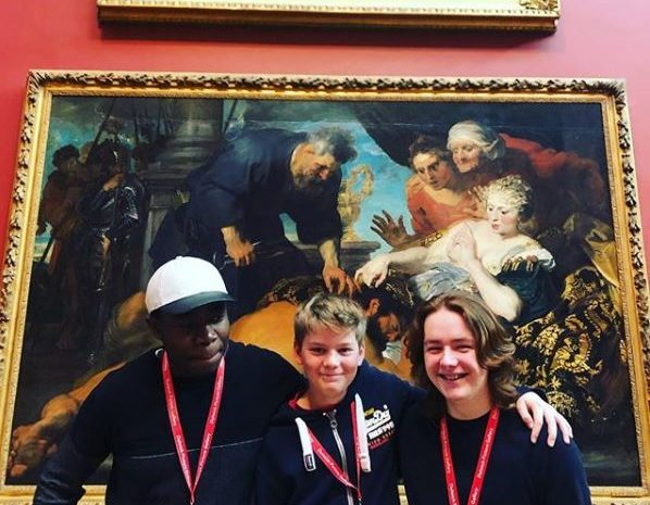 Three young people standing in front of a painting at Dulwich Art Gallery during their Instagram takeover.