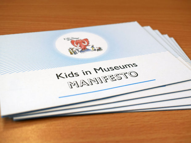 A pile of paper copies of the Kids in Museums Manifesto lying on a table.