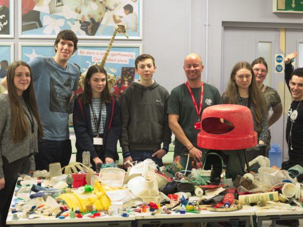 Members of the youth forum standing behind a table covered with plastic found on Welsh beaches at National Museum Cardiff.