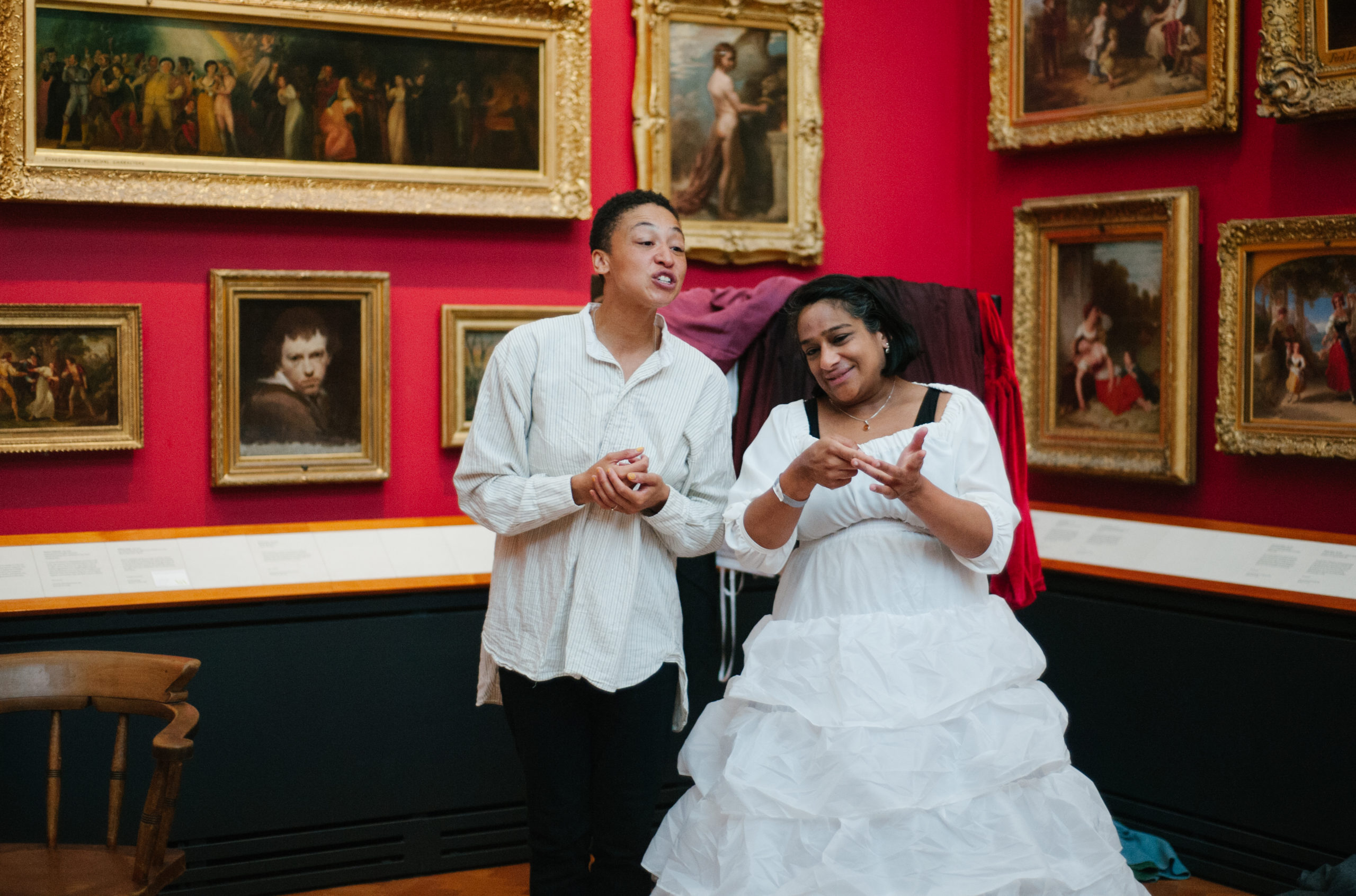 Two actors dressed in historical clothing perform and sign in a gallery at the Victoria and Albert Museum, London.