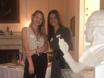 Two young people wearing Takeover Day badges stand in front of a statue of a bust holding a mobile phone.