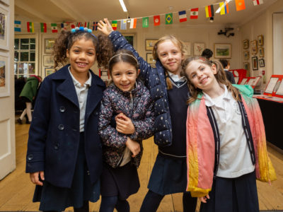 A group of children smile in front of their exhibition at Lauderdale House.