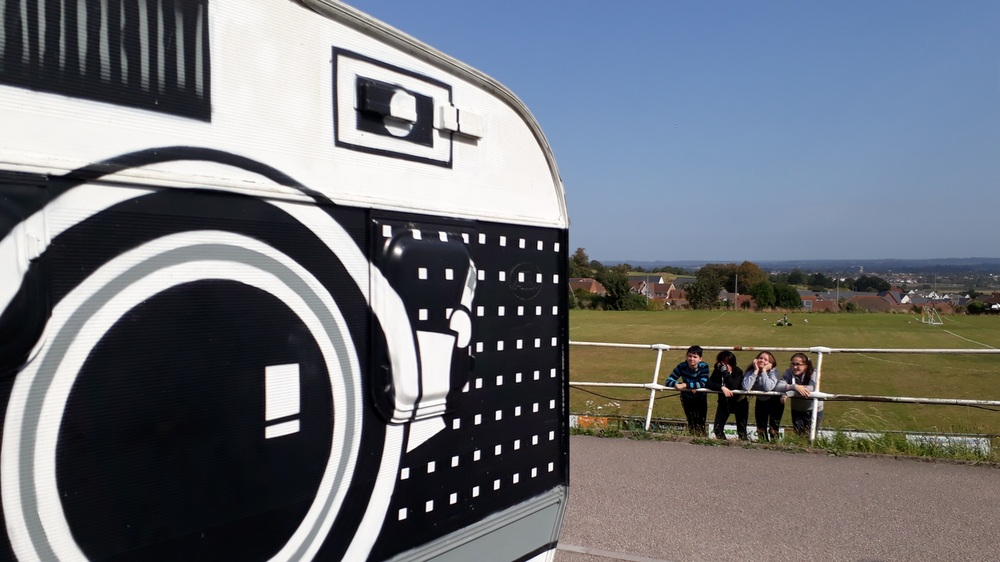 Four young carers lean on a fence next to a caravan painted to look like a giant camera.