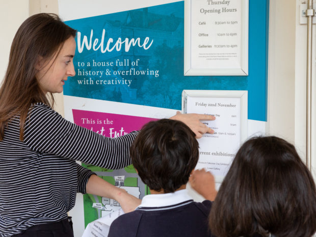 A member of staff helps two children put up a sign to advertise their Takeover Day at Lauderdale House.