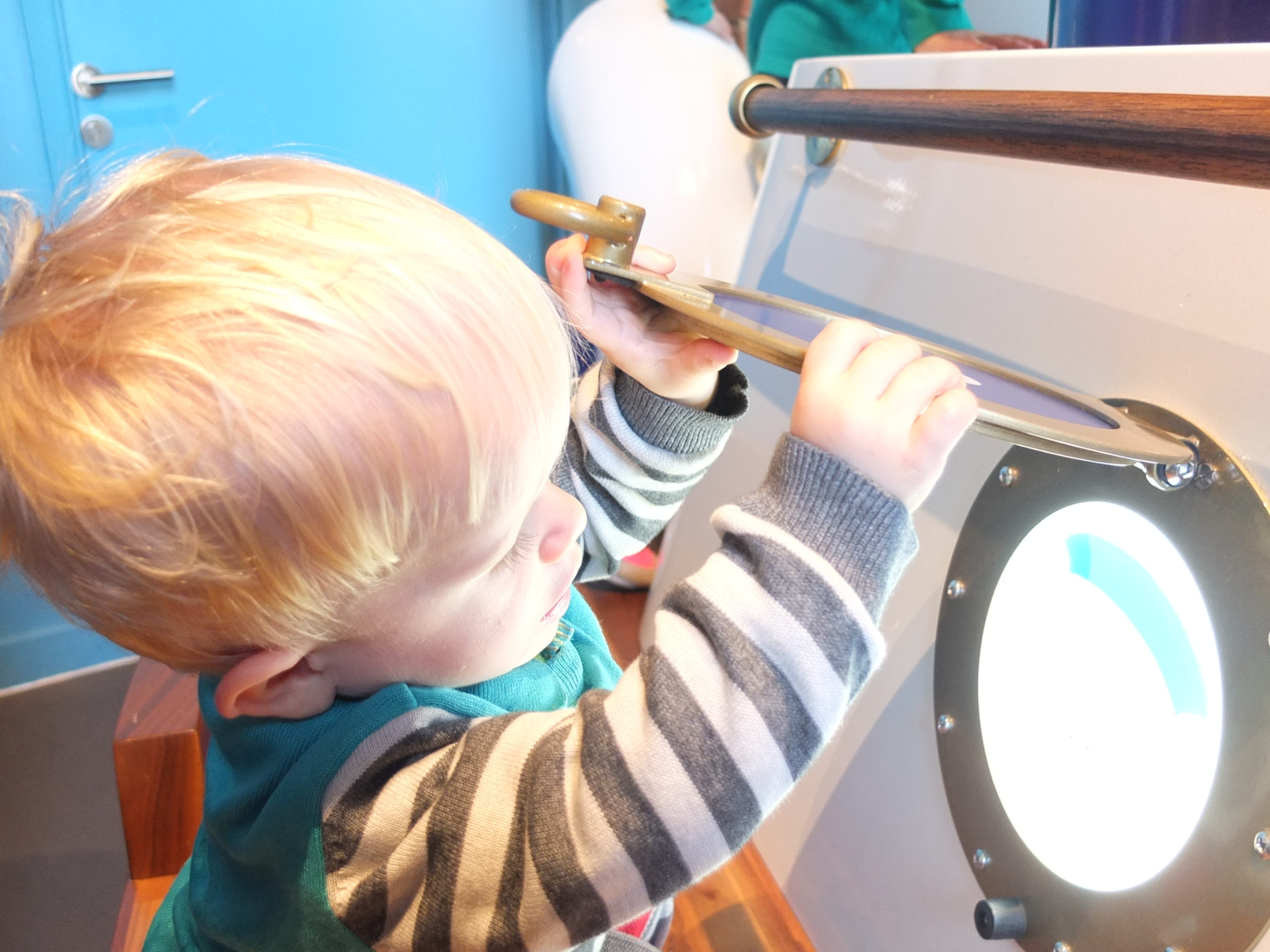 A toddler stands and lift a porthole window up.