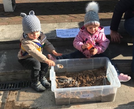 Two small children in winter coats and hats play with sand in a plastic box on the concrete steps outside the museum.