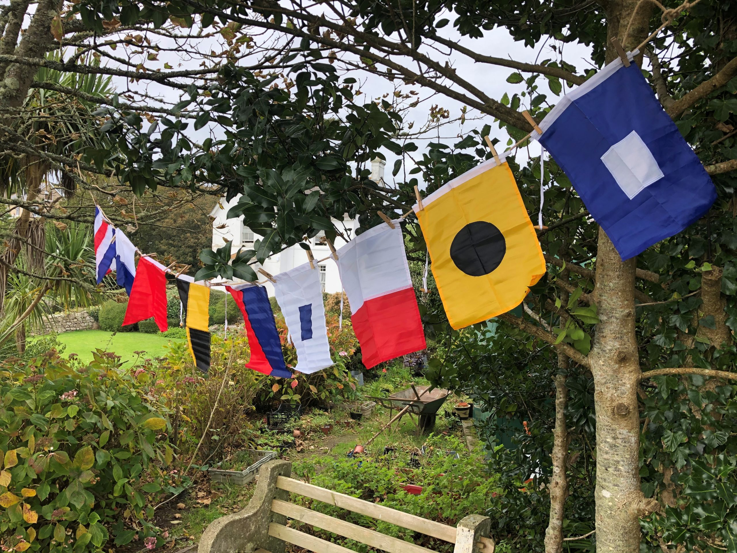 A line of fabric flags hanging in a garden above a wooden bench.