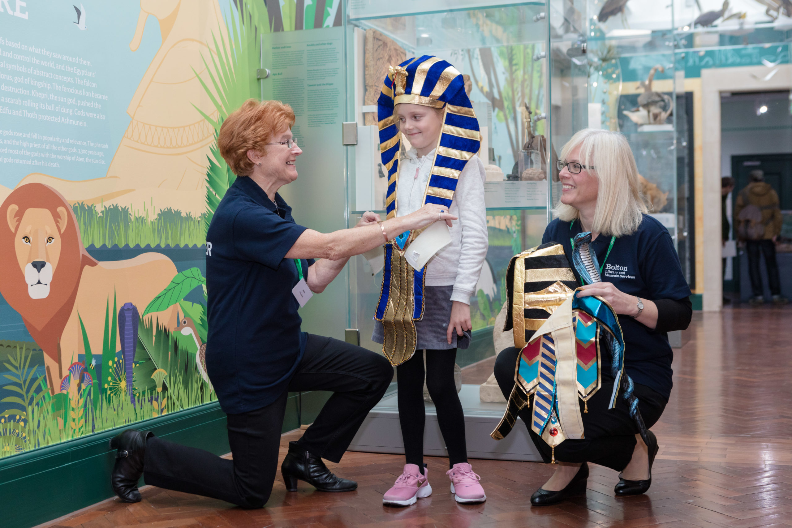 Two women kneeling help dress a young girl standing up in Ancient Egyptian costume in a gallery at Bolton Museum.