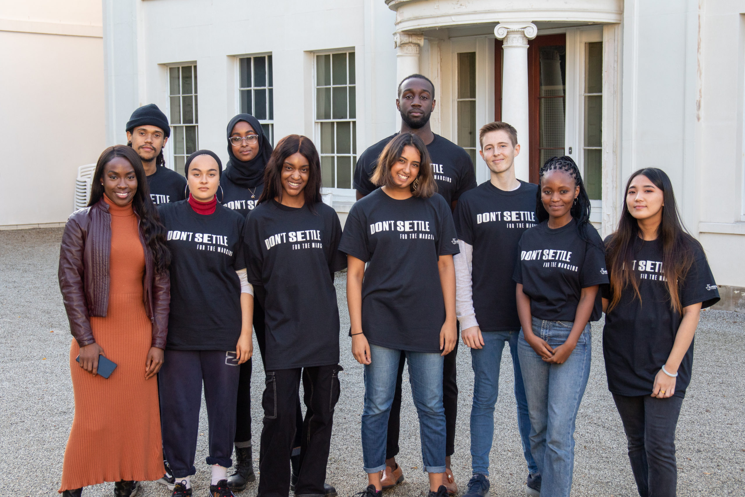 A group of young people wearing black t shirts reading Don't Settle in white text smiling and standing in front of a historic white building.